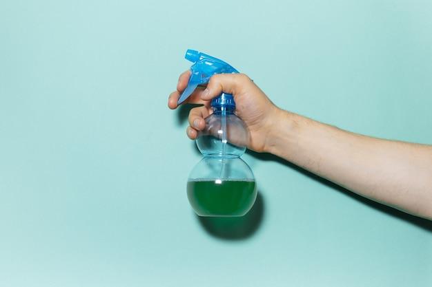 Primo piano della mano maschio che tiene il flacone spray per la pulizia con pompa blu