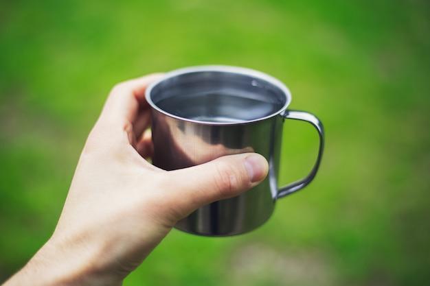 Primo piano della mano maschio che tiene tazza d'acciaio con acqua su sfondo sfocato.
