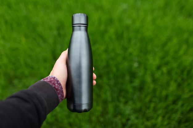 Primo piano di una bottiglia d'acqua termica riutilizzabile in acciaio che tiene la mano maschile su sfondo di erba verde sfocata. Foto Premium