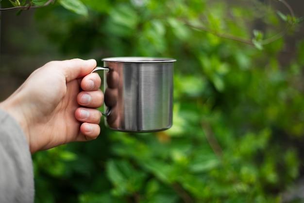 Primo piano della mano maschio che tiene la tazza termica d'acciaio sul cespuglio verde nel bokeh