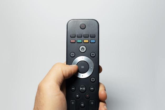Primo piano della mano maschio che tiene il telecomando della tv su briciolo