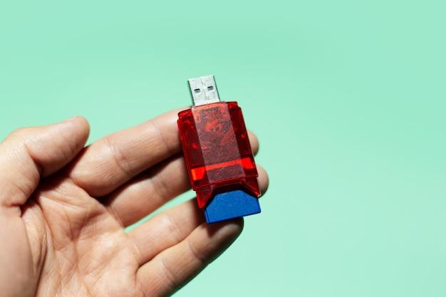Primo piano della mano maschio che tiene adattatore flash usb per scheda sd isolato