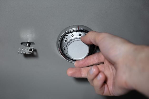 Primo piano della mano maschio, introduce il codice di sicurezza di combinazione della serratura della cassaforte.