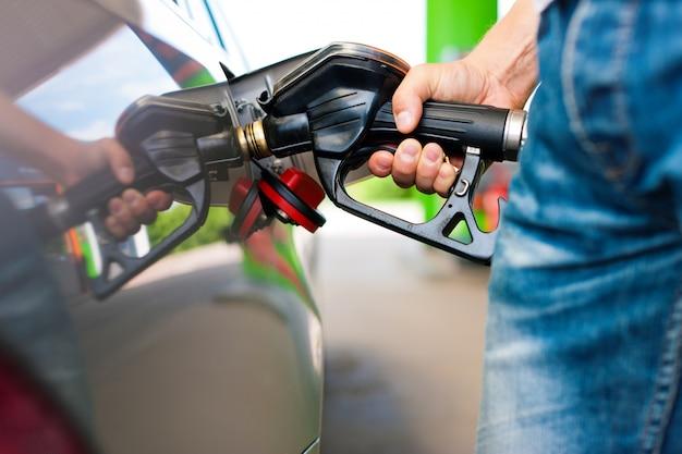 Primo piano di un'automobile maschio di rifornimento di carburante della mano alla stazione di servizio