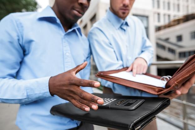 Il primo piano del maschio consegna il documento. due uomini d'affari credono le entrate e le spese su una calcolatrice