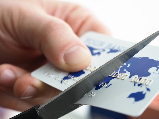 Primo piano delle mani maschii che tengono la carta di plastica e che tagliano a metà con le forbici. uomo d'affari cambiando bankcard con mappa del mondo e numero. conti da pagare e concetto di denaro
