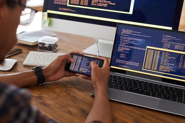 Chiuda in su delle mani maschii che tengono smartphone con codice sullo schermo mentre si lavora alla scrivania in ufficio, concetto di sviluppatore it, spazio di copia