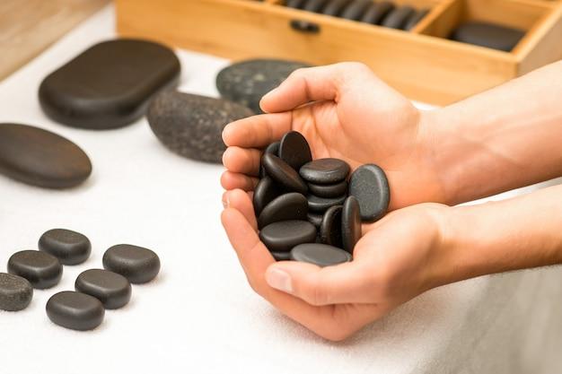 Chiuda in su delle mani maschili che tengono i ciottoli neri della stazione termale nei suoi palmi sopra un tavolo bianco nel salone della stazione termale