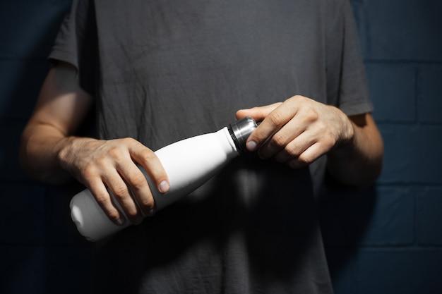 Primo piano delle mani maschile, apre la bottiglia d'acqua termica in acciaio di colore bianco, sullo sfondo del muro di mattoni neri.