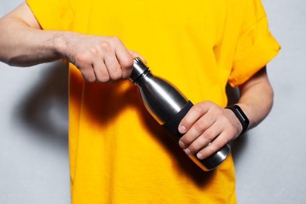 Il primo piano delle mani maschili apre la bottiglia di metallo riutilizzabile