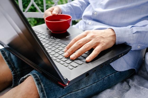 Primo piano di mani maschile utilizzando laptop