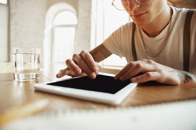Primo piano delle mani maschili utilizzando tablet con schermo vuoto, copyspace. navigare, fare acquisti online, scorrere, scommettere, lavorare. istruzione, freelance, arte e concetto di business. guardare il cinema, leggere libri.