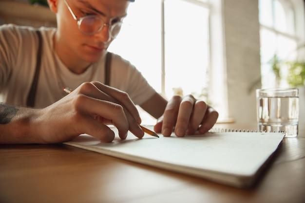 Primo piano di mani maschili che scrivono su un foglio vuoto sul tavolo di casa
