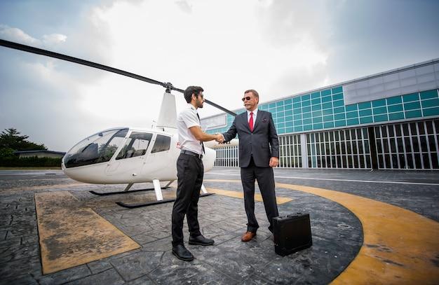 Primo piano di un pilota di elicottero maschio indossare occhiali da sole e uomini d'affari o ceo esecutivo in piedi contro l'elicottero al punto di atterraggio degli aerei in aeroporto in una luminosa giornata di sole.