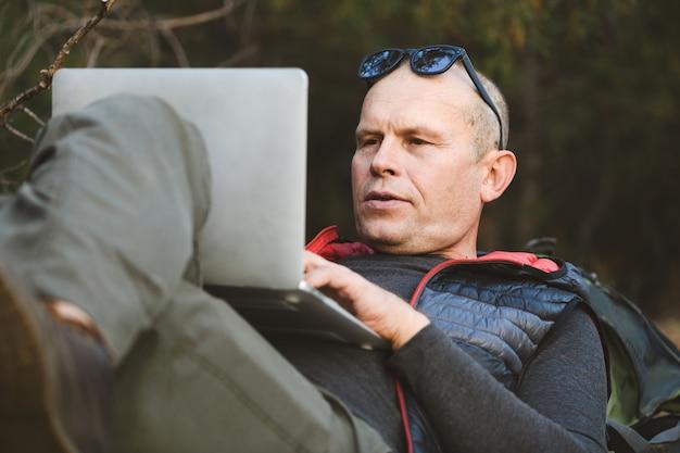 Primo piano di un escursionista maschio sdraiato sulla schiena appoggiato allo zaino, con computer portatile, digitazione, blog, navigazione nella foresta