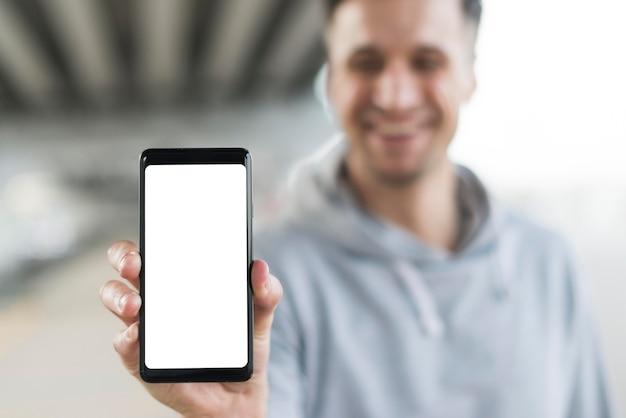 Telefono cellulare maschio della tenuta del primo piano