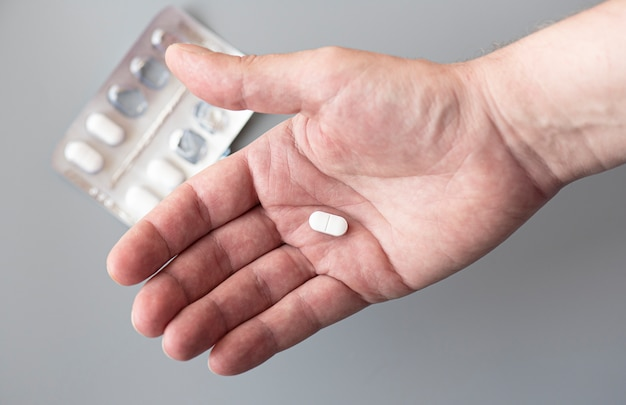 Palma maschio del primo piano con una compressa. equipaggi la tenuta della pillola bianca in sua mano, immagine di concetto.