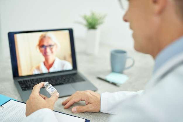 Primo piano del medico di sesso maschile che tiene in mano una bottiglia di vaccino contro il coronavirus e utilizza il laptop per la comunicazione online in clinica