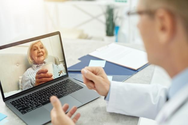 Primo piano di un medico maschio seduto al tavolo con il taccuino e che parla con una vecchia signora allegra tramite videochiamata