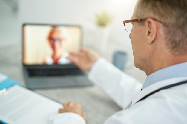 Primo piano del medico maschio seduto al tavolo con il taccuino e parlare con la paziente tramite videochiamata