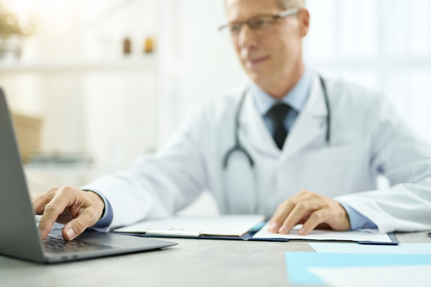 Primo piano del medico maschio seduto al tavolo con documenti e digitando sulla tastiera del laptop laptop