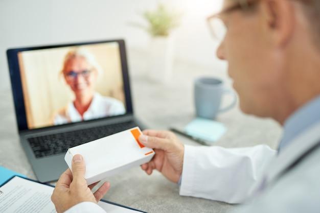 Primo piano di un medico maschio con farmaci in mano seduto al tavolo con il taccuino e parlando con un collega tramite videochiamata