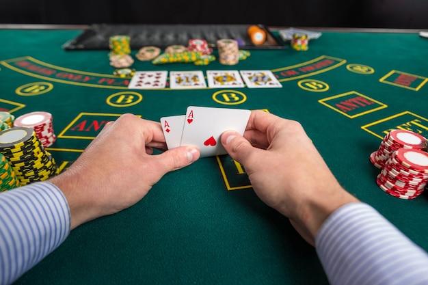 Primo piano del giocatore di poker maschio che solleva gli angoli di due carte assi al tavolo del casinò verde con assi