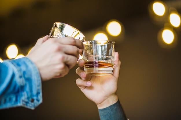 Primo piano della mano del maschio che tosta bicchiere di bevande contro il fondo del bokeh