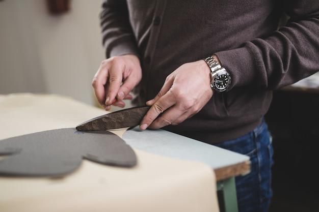 Primo piano di un calzolaio maschio che lavora con tessuti in pelle nel suo laboratorio.