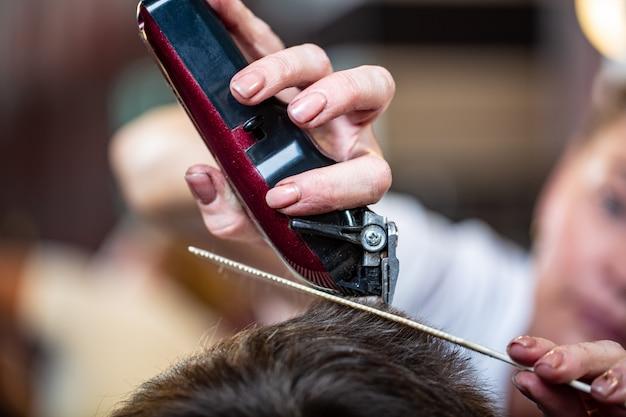 Chiuda in su di uno studente maschio che ha un taglio di capelli con le tosatrici