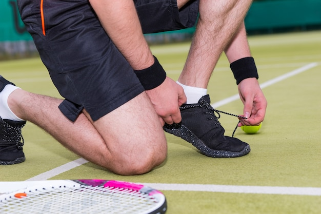 Chiuda sul giocatore di tennis maschio che lega i lacci delle scarpe a sinistra della racchetta e della palla su un campo all'aperto in estate o in primavera