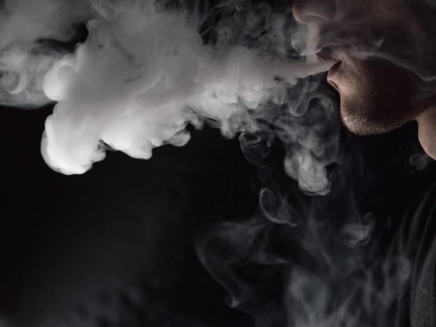 Primo piano di un vaper maschio che espira una nuvola di vapore