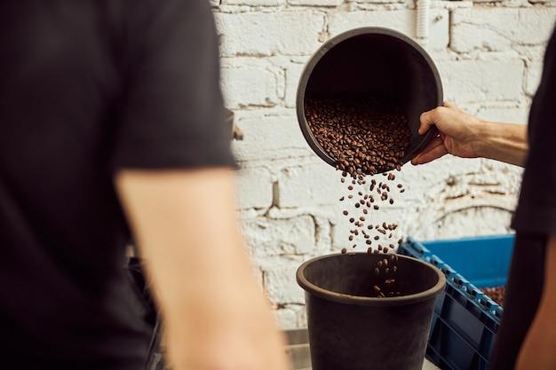 Primo piano di lavoratori di sesso maschile che controllano e selezionano i chicchi di caffè tostati in magazzino in