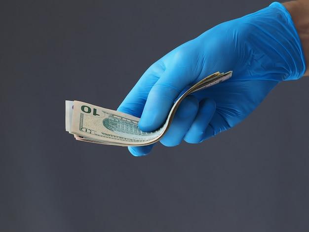 Avvicinamento. l'uomo in guanti blu tiene i dollari americani. sfondo grigio.
