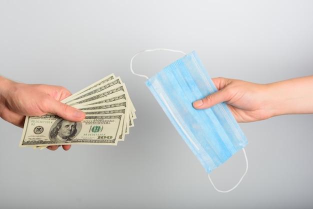 Primo piano di un uomo che compra una maschera medica. il concetto di forte domanda. vendita di maschere mediche blu per dollari.