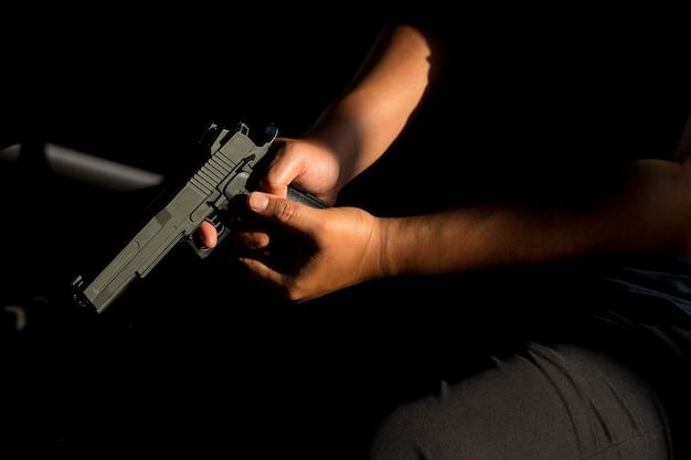 Primo piano di un uomo che porta una pistola al buio