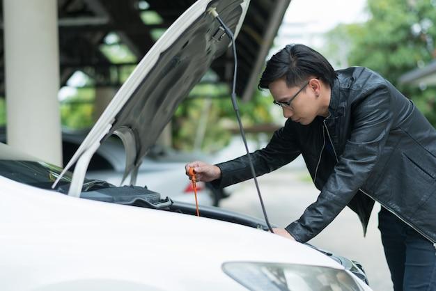 Chiuda sull'uomo che controlla il livello dell'olio in un'auto
