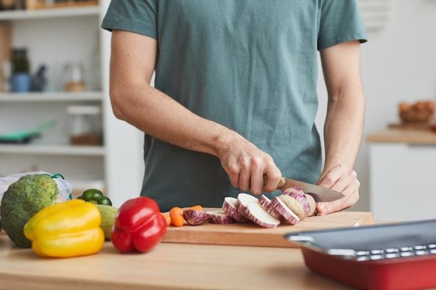 Primo piano dell'uomo che taglia le verdure con il coltello sul tagliere in cucina