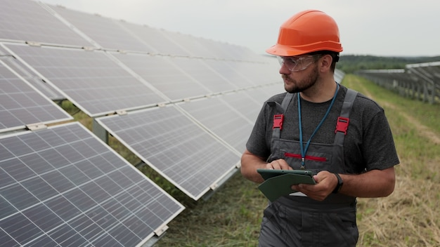 Primo piano di un ingegnere in abiti da lavoro cammina sulla stazione di energia rinnovabile che tiene tablet digitale e controlla l'installazione dei pannelli solari. tecnologia. concetto ecologico.