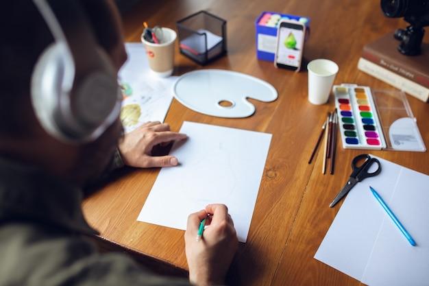 Primo piano dell'uomo che dà lezioni di disegno online a casa registrazione del tutorial degli insegnanti sulla fotocamera