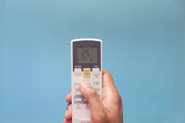 Chiuda in su della mano dell'uomo che tiene il telecomando dello stato dell'aria.