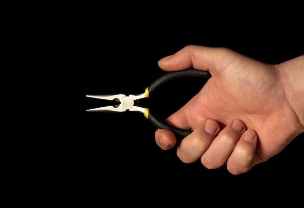 Primo piano della mano dell'uomo che tiene le pinze diagonali