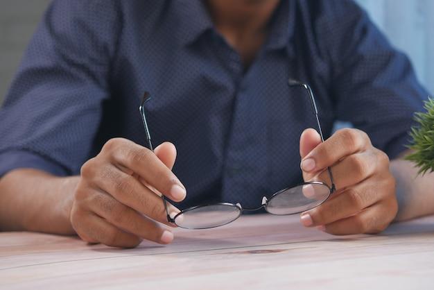 Primo piano della mano dell'uomo che tiene il vecchio occhiale