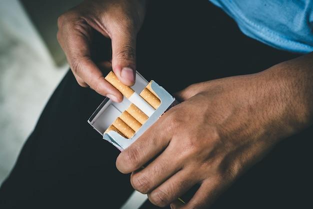 Chiudere la mano dell'uomo che tiene staccarlo dal pacchetto di sigarette preparare il fumo di una sigaretta. linea di imballaggio. diffusione del fumo di sigaretta.