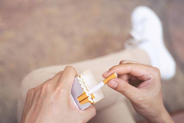 Close up man mano che tiene la buccia fuori pacchetto di sigarette preparare fumare una sigaretta. linea di imballaggio.