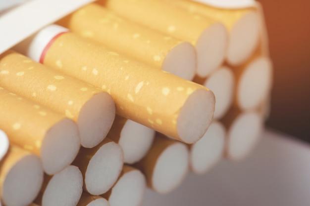 Close up man mano che tiene la buccia fuori pacchetto di sigarette preparare fumare una sigaretta.