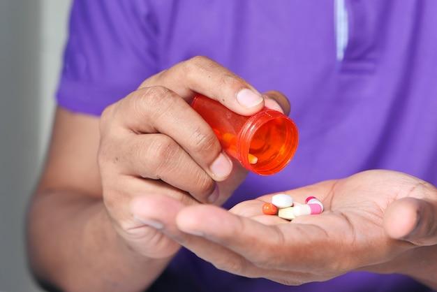 Chiuda in su della mano dell'uomo che cattura la medicina.