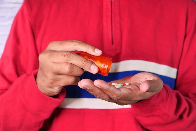 Chiuda in su della mano dell'uomo che cattura la medicina