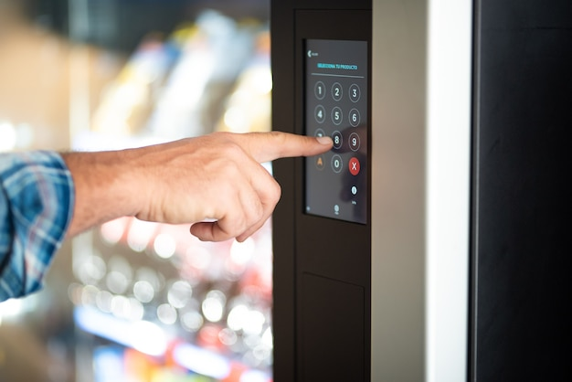 Primo piano della mano dell'uomo che digita il codice numerico sul display touch screen - concetto di password di sicurezza e cibo distributore automatico - tipo di dito maschio caucasico 8