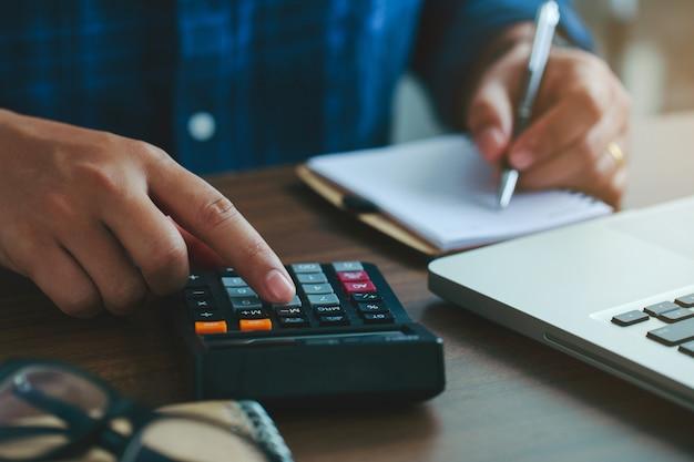Chiudere la mano dell'uomo usando una calcolatrice per calcolare i numeri e l'altra mano sta prendendo appunti
